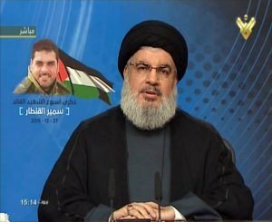 "An image grab taken from Hezbollah's al-Manar TV on December 27, 2015, shows Hassan Nasrallah, the head of Lebanon's militant Shiite Muslim movement Hezbollah, giving a televised address from an undisclosed location in Lebanon on the one-week anniversary of the killing of Samir Kantar (portrait-L), one of the party's top militants, in a suspected Israeli air strike in Damascus.  AFP PHOTO / HO / AL-MANAR    === RESTRICTED TO EDITORIAL USE - MANDATORY CREDIT ""AFP PHOTO / HO / AL-MANAR"" - NO MARKETING NO ADVERTISING CAMPAIGNS - DISTRIBUTED AS A SERVICE TO CLIENTS ==="